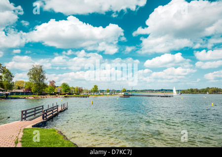 Lake Chiemsee in Germany with sailboat and bright sun. - Stock Photo