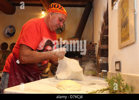 Torre Alfina, Italy, pizza baker pollinated a pizza dough with flour - Stock Photo