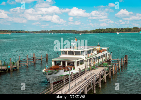 Passenger ship on lake Chiemsee in Germany with sailboat and bright sun. - Stock Photo