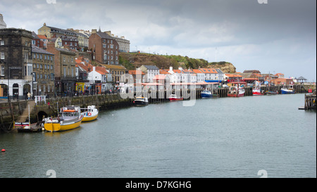Yellow pleasure boats and blue and red fishing boats tied up at the fish quay in Whitby harbour North Yorkshire. - Stock Photo