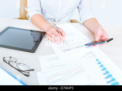 Successful businesswoman sitting at desk in casual clothes and using modern devices for analyzing sales statistics - Stock Photo