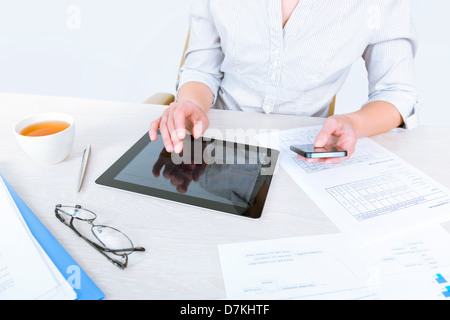 Successful businesswoman sitting at desk and simultaneously using modern devices for business communication - Stock Photo