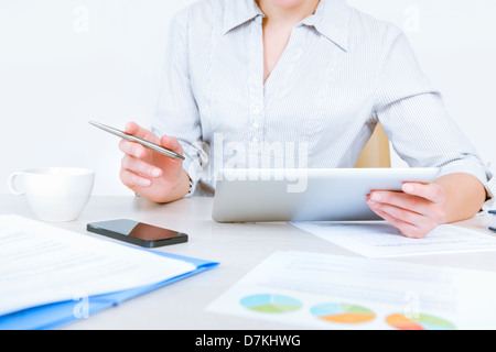 Relaxed businesswoman wearing casual shirt sitting at desk and working with data on digital tablet in the office - Stock Photo