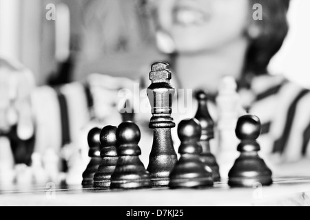 Black chess pieces on a chess board with a little boy in the background - Stock Photo