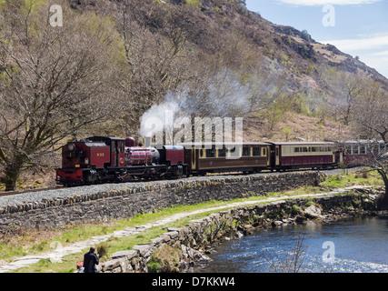 Welsh Highland Railway steam train travelling along Aberglaslyn Pass by Afon Glaslyn River in Snowdonia National Park. Beddgelert North Wales UK