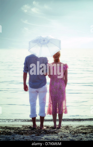 a couple on the beach with a parasol - Stock Photo