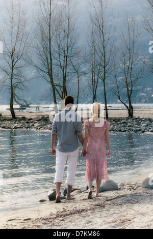 a couple is walking on the beach - Stock Photo