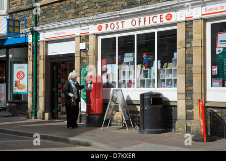 Middle-aged woman posting letter outside Windermere Post Office, Lake District National Park, Cumbria, England UK - Stock Photo