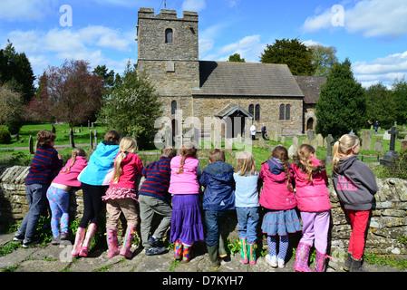 Children resting on wall of Stokesay Castle, showing St John the Baptist Church, Stokesay, Shropshire, England, - Stock Photo