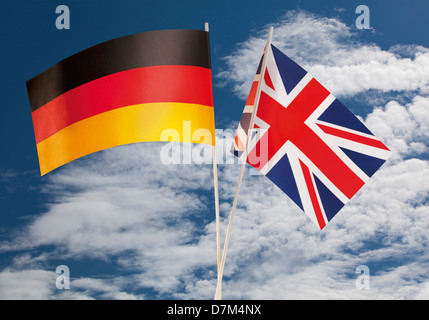 English flag and German flag against cloudy sky - Stock Photo