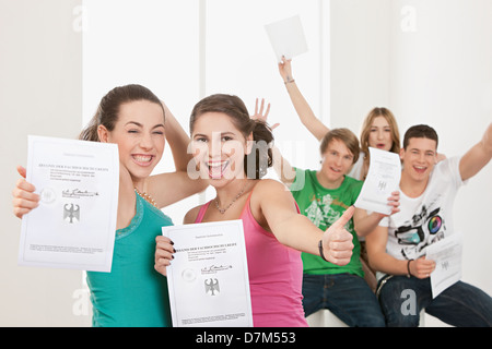 Young people with High School Diploma, smiling, portrait - Stock Photo