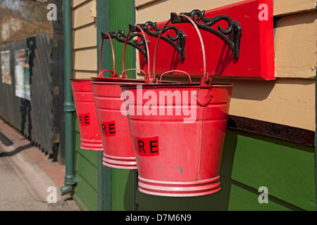 Close up of Three traditional red fire buckets bucket at Pickering Railway Train Station North Yorkshire England UK United Kingdom GB Great Britain