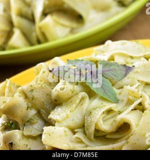 Pasta tagliatelle with pesto sauce and basil - Stock Photo