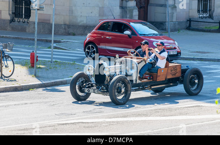 2 men driving a blue convertible Bugatti French vintage car - Stock Photo