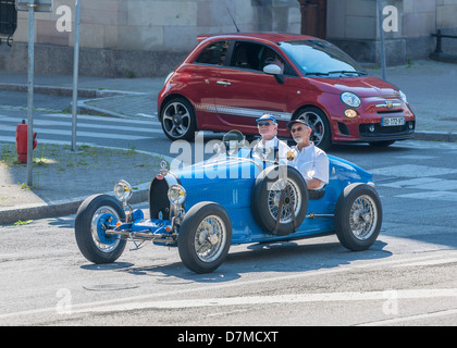 2 elderly men driving a blue convertible Bugatti French vintage car - Stock Photo
