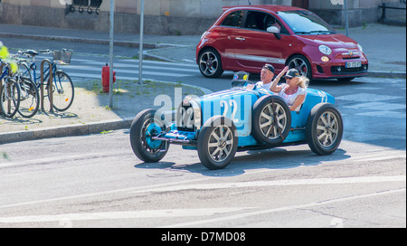 Couple driving a blue convertible Bugatti French vintage car - Stock Photo