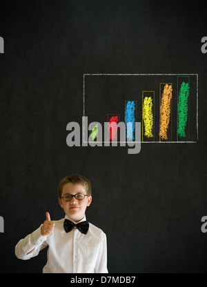 Thumbs up boy dressed up as business man with chalk graph or chart on blackboard background Stock Photo