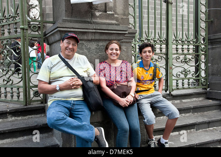 happy smiling Mexican family with teenage son sit on stone steps outside wrought iron fence of Cathedral entrance - Stock Photo