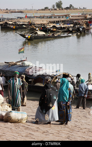 Local men and women waiting to buy fish from fishing boats, early morning, Mopti fish market on River Niger, Mali - Stock Photo