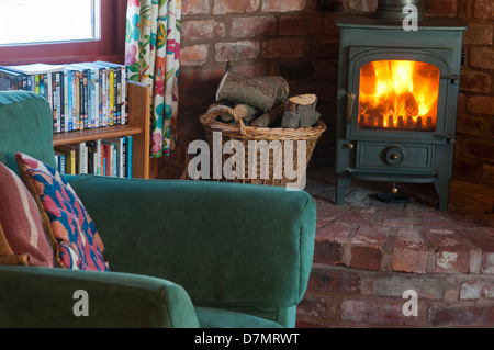 Wood burning stove in Shropshire cottage with log basket and armchair - Stock Photo