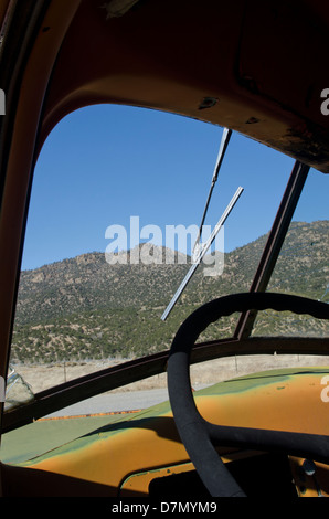 An old antique truck rusts slowly in a mountain field, but its front windshield and wiper are still intact. - Stock Photo