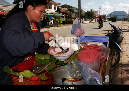 A noddle vendor in Vang Vieng pours spicy soup onto rice noodles, now ready to serve. - Stock Photo