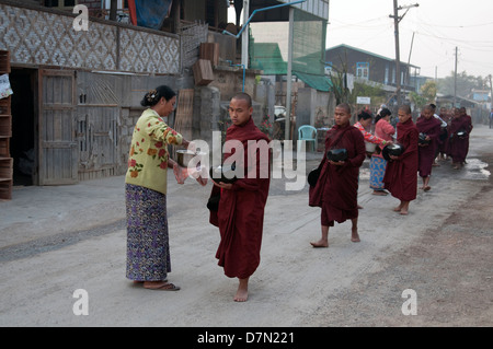 A line of Buddhist monks receive offerings of rice alms from locals near Inle lake Myanmar (Burma) - Stock Photo