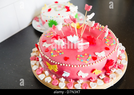 Colorful decorated white and pink Marzipan cakes for a birthday party on kitchen dresser - Stock Photo