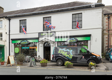 The 3 Peaks Cycles shop and company van on Market Place in Settle, North Yorkshire. - Stock Photo
