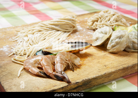 Shrimp, mussels, dim sum, and pasta on a cutting board.  Korean restaurant - Stock Photo