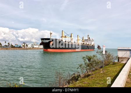 Freighter transporting grain, entering Port Of Corpus Christi. - Stock Photo