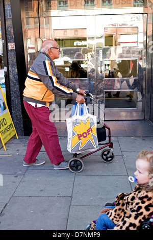 An old man dressed in youthful clothing  walks with the aid of  a walking frame. - Stock Photo