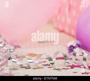 silver party streamers on party table with confetti and baloons - Stock Photo