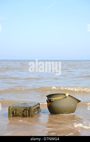 An American WW2 helmet & ammo box on the beach with the tide coming in. - Stock Photo