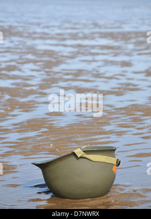 An American WW2 helmet sitting upside down on the beach with the tide out. - Stock Photo