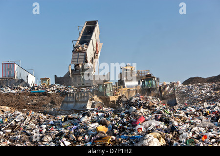 Landfill, tractor compactors pushing trash.  Tipper dumping semi trailer containing collected garbage. - Stock Photo
