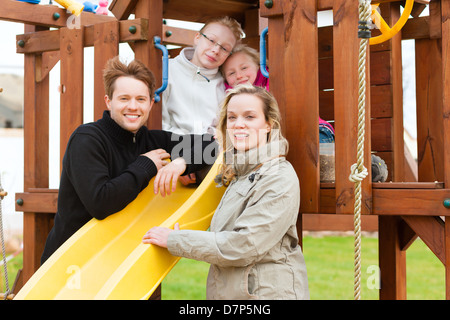 Young Family on the playground, the children sitting on a climbing frame, mother and father standing in front - Stock Photo