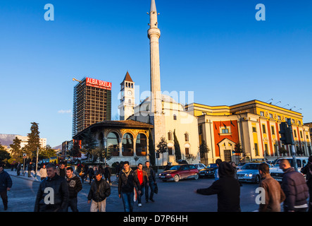 People crossing Skanderbeg Square with Ethem Bey mosque in background. Tirana, Albania - Stock Photo