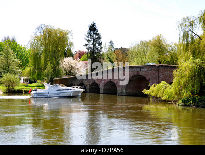 Berks - Sonning on Thames - river cruiser approaching the old bridge - sunlight - reflections - wooded backdrop - Stock Photo