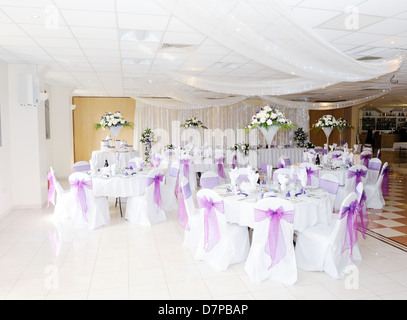 Wedding reception interiot showing tables and chairs decorated in white and purple - Stock Photo