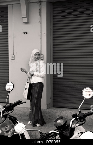 PHUKET, THAILAND OCTOBER 1 2011: A Thai Muslim woman watches a street procession during the annual Phuket Vegetarian - Stock Photo