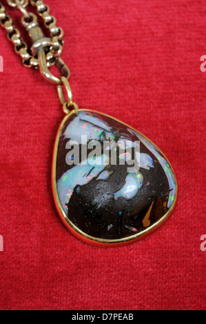 Wood opal pendant against a red background. - Stock Photo