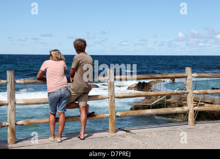 Couple Looking Out to Sea at  Bronte during a scenic stop on the Bondi to Coogee Walk in Australia - Stock Photo