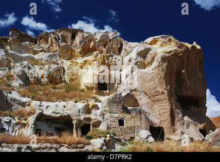 Rock carved medieval houses in Urgup, Cappadocia in Turkey, central Anatolia. - Stock Photo