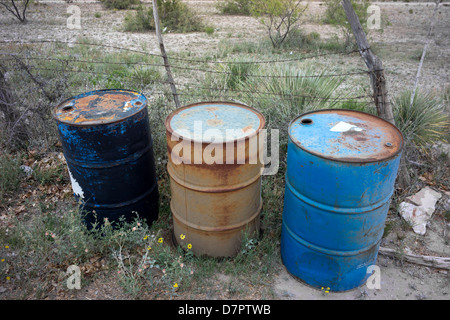 Oil drums abandoned by a side of a road in West Texas. - Stock Photo
