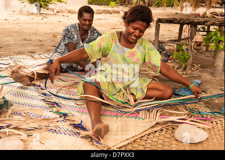 Traditional village life, two women in colourful dresses weaving mats for guests to a large church meeting in their - Stock Photo