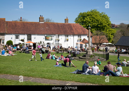 English village pub The Tiger at East Dean, East Sussex. Busy on a bank holiday Monday ppl sit on the green and - Stock Photo