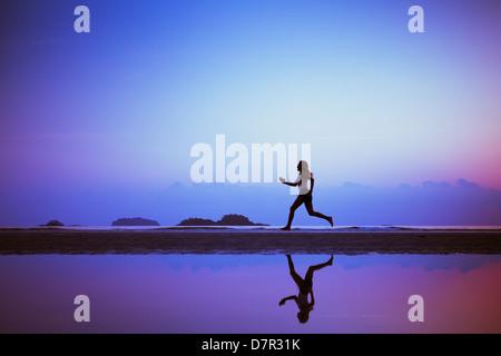 sport background, run to purpose, woman silhouette on the beach - Stock Photo