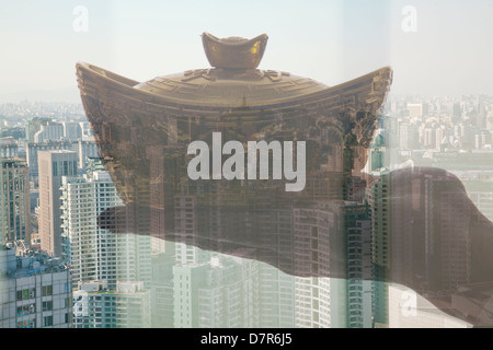 Holding Chinese New Year Gold Ingot, Day City View - Stock Photo