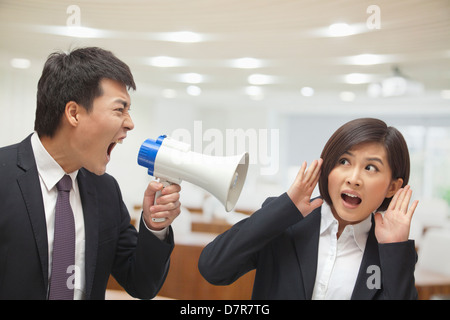Businessman Talking into Megaphone by Businesswoman's Ear - Stock Photo